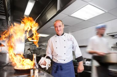 A London chef with flames photographed for a corporate brochure portrait