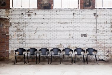 A row of contemporary black chairs in an abandoned power station