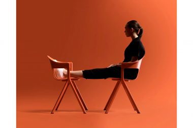 A woman sat oin an orange chair in a studio phoptograph