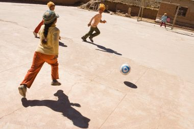 An advertising campaign image of children playing football