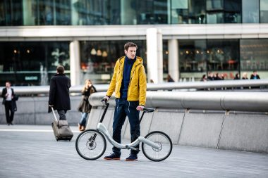 An advertising lifestyle photograph of a man with a bicycle