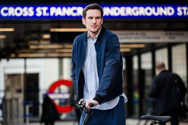A man with a bicycle in front of a London Underground sign