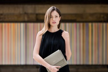 An advertising photograph of a woman with a luxury handbag