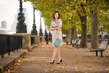 a woman photographed in London holding a luxury fashion handbag
