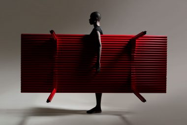 Photograph of a woman holding a red table in a photographic studion in London