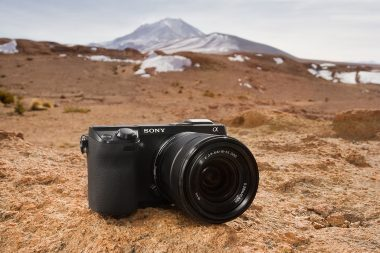An advertising photograph of a Sony camera in a landscape