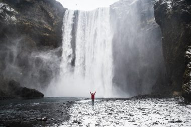 A lifestyle photograph of a woman in front of a waterfall in Iceland
