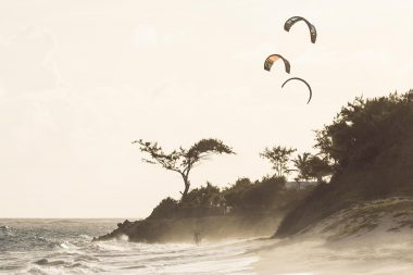 Advertising lifestyle photograph of kitesurfers on a beach in Barbdos caribbean