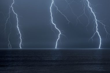 Photograph of lightning forks over the sea at night
