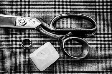 Close up photograph of tailors scissors and chalk on material at a Savile Row tailors