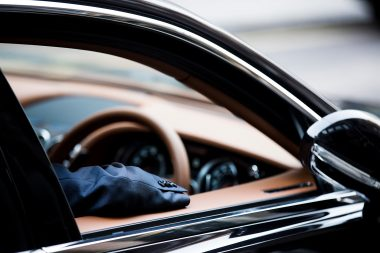 Man with elbow on window of luxury car in London