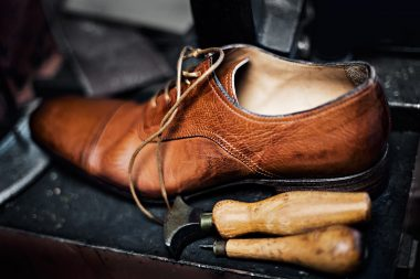 Mens leather shoe with tools on a workbench