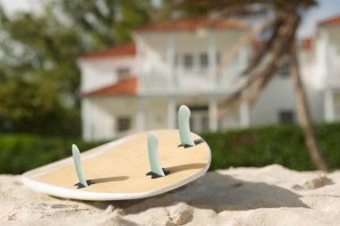 Surf board on a beach with beach house in the background in Barbados