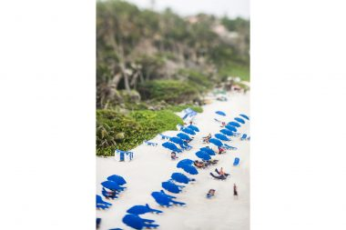Lifestyle photograph of prople on beach in Barbados with blue umbrellas