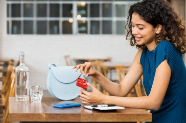 Lifestyle-photograph-of-a-woman-in-cafe-with-charging-device