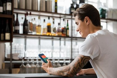 Man-in-London-bar-holding-mobile-phone-lifestyle-photograph