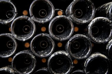 old-wine-bottles-in-the-cellar-of-the-olivier-bernstein-winery-in-beaune-france